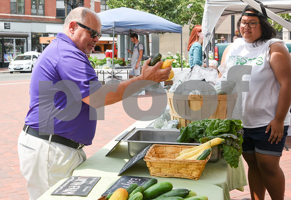 071217 Wesley Bunnell   Staff The first farmers market of the year in Central Park took place on Wednesday featuring local businesses and pizza truck. Executive Director at New Britain Downtown District's Gerry Amodio chooses vegetables grown by Urth Farms from the New Britain Roots truck.
