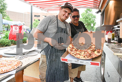 071217  Wesley Bunnell | Staff  The first farmers market of the year in Central Park took place on Wednesday featuring local businesses and pizza truck. Frank Bernardo Jr. , L, and Frank Bernardo Sr. stop to pose with one of their creations.