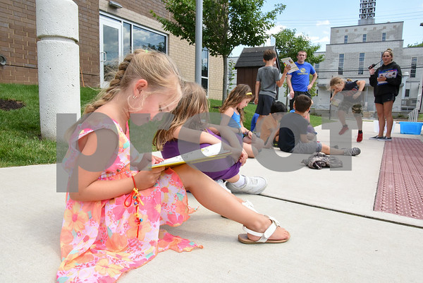 070517 Wesley Bunnell   Staff Rylee Keeley, age 6, reads One Fish, Two Fish, Three Fish, Blue Fish by Dr. Seuss outside of the Bristol Boys and Girls Club. The books are from the Bristol Board of Education Book Mobile which made a visit to the club.