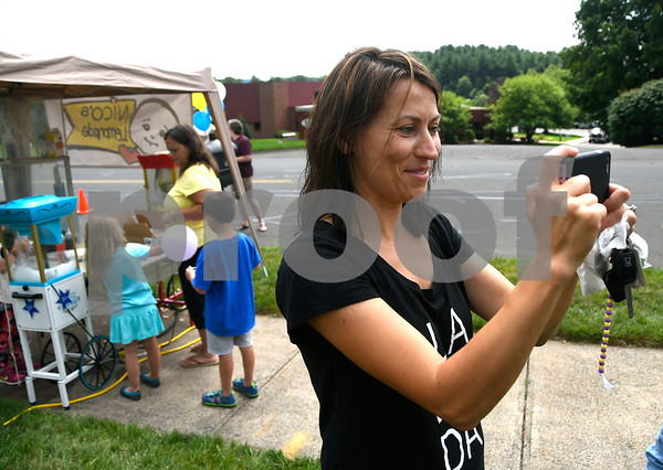 7/15/2017 Mike Orazzi | Staff Beata Mizerek takes a photograph during Nico's Lemonade Stand fundraiser on Northwest Drive in Plainville Saturday.