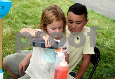 7/15/2017 Mike Orazzi | Staff Nico Fasold oversees as Riley Cambi as she makes a snow cone during  Nico's Lemonade Stand  fundraiser on Northwest Drive in Plainville Saturday.
