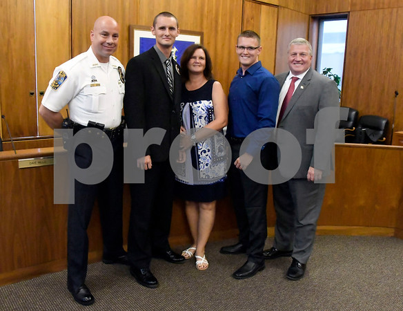 7/6/2017 Mike Orazzi | Staff Future Bristol police officer John D. Clary after taking the oath to become a Bristol police officer during a ceremony at city hall Thursday afternoon. Left to right, chief Brian Gould, Clary, his mom Alisa, twin brother Adam and Bristol Mayor Ken Cockayne.