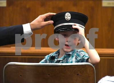 7/6/2017 Mike Orazzi | Staff Bristol Fire Department's Todd Correll reaches for his cap worm by his son Charlie prior to his promotion to captain at Bristol City Hall Thursday.