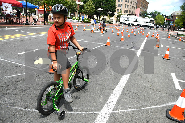 7/8/2017 Mike Orazzi | Staff Christopher Garcia,7, watches as professional bike riders perform stunts during the 4th Annual Bike Safety Day in downtown New Britain Saturday.