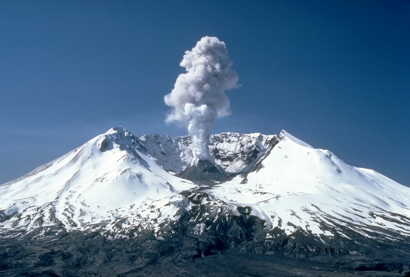 """Mt St Helens, on a clear day, with a puff of smoke from """"geologic events"""" taking place under the surface.  This is a fairly recent picture and was taken well after the 1980 blast that took off the entire top of the mountain.  There is a cone in the center (where the smoke is coming from) and that cone grows by feet per year as small eruptions happen and the lava gradually forms a new mountain top. <br /> <br /> (Photo from Wikipedia)"""