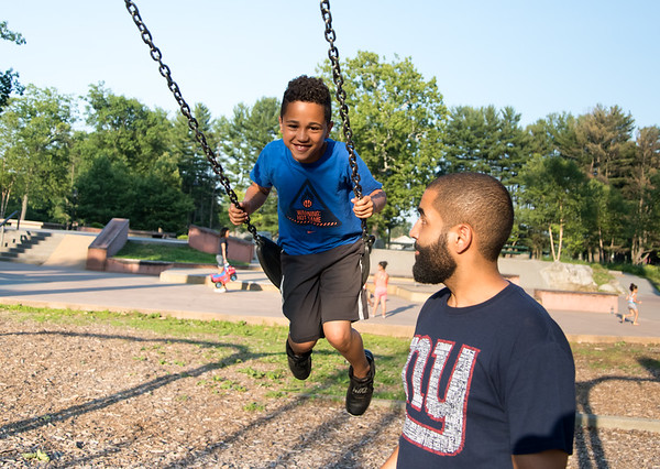 07/02/18 Wesley Bunnell | Staff Caleb Roman, age 10, plays on the swing set at Rockwell Park on Monday evening with his father Luis Roman.