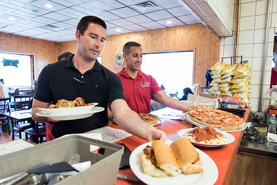 06/07/18  Wesley Bunnell | Staff  Berlin Police Officers Ted Fuini, L, and Brandon Lageaux pick up their orders to be served from the kitchen in the departments annual Tip A Cop event at Central Pizza on June 7.