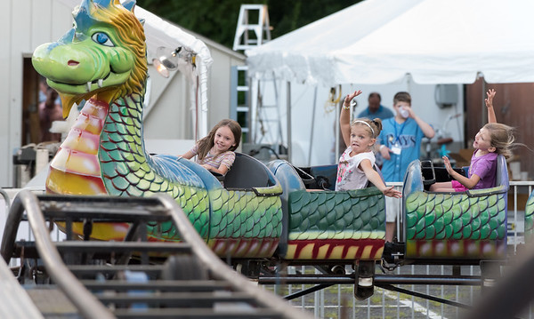 07/12/18 Wesley Bunnell | Staff Five year old Nora Sparkman, L, and twin Chloe, R, enjoy riding the Dragon ride on the first night of the Holy Cross Church's Sixty-'Fourth Bazaar and Carnival on Thursday night.