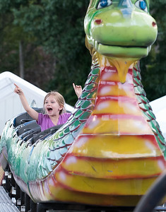 07/12/18  Wesley Bunnell | Staff  Five year old Chloe Sparkman points to her family as she rides the the Dragon ride on the first night of the Holy Cross Church's Sixty-'Fourth Bazaar and Carnival on Thursday night.