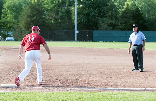 07/12/18 Wesley Bunnell | Staff Berlin Legion baseball vs RCP at Sage Park on Thursday evening. Berlin's first base coach demonstrates to the umpire how he felt the RCP first baseman came off the base during a close play at first that resulted in the Berlin runner being doubled off.