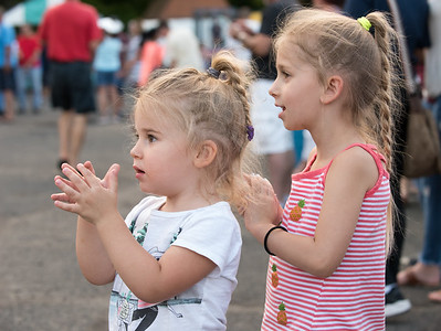 07/12/18  Wesley Bunnell | Staff  Vivienne, L age 2, and Quinn Previti, age 4, clap as they listen to the Polish singers on the first night of the Holy Cross Church's Sixty-'Fourth Bazaar and Carnival on Thursday night.