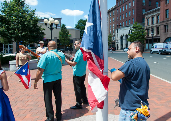 07/20/18 Wesley Bunnell | Staff A city worker attaches the Puerto Rican flag to a flag pole at Central Park on Friday at noon. The Puerto Rican flag was raised in Central Park recognition of Saturday's Puerto Rican Festival.