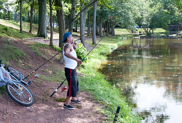 07/24/18 Wesley Bunnell | Staff Ramon Rodriguez holds one fishing pole while checking the line of another while fishing at Stanley Quarter Park on Tuesday afternoon.