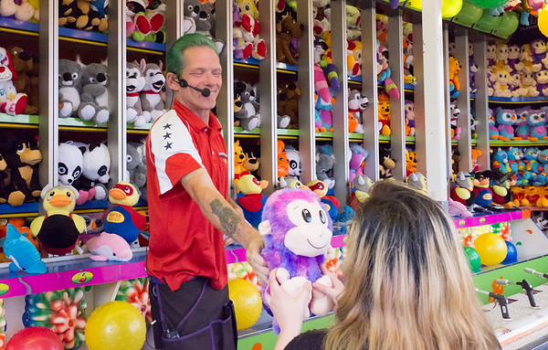 07/03/18 Wesley Bunnell | Staff A worker hands a prize to Makayla Gonzales at the Berlin Fairgrounds on Tuesday night. From Tuesday through Saturday Dreamland Amusements is holding Freedom Fest at the the Berlin Fairgrounds featuring carnival rides, entertainment and fireworks on Wednesday and Saturday at 9:30pm.