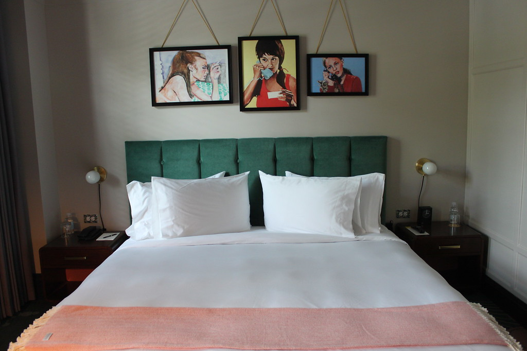 Green tufted hotel bed with white sheets and pink blanket, paintings of women above