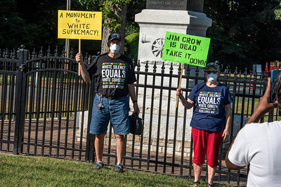 Several protestors stood at the fence surrounding the base of the statue with signs and shirts that expressed their opinions. (Bill Giduz photo)
