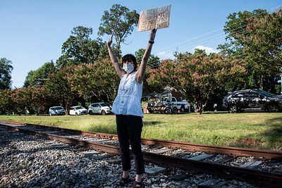 """Diane Means stood at the railroad tracks to make sure drivers passing by took notice. One of her signs read: """"At Heritage of Hate is Nothing to Celebrate."""" (Bill Giduz photo)"""