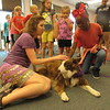 CATHY SPAULDING/Muskogee Phoenix<br /> Denise Gard, a storyteller from Colorado, brought two border collies to Q.B. Boydstun Library on Friday to help the library celebrate the conclusion of its 2018 Summer Reading Program. Gard, left, lets McKenzie Colbert, 9, pet Sienna, one of the two border collies she brought.