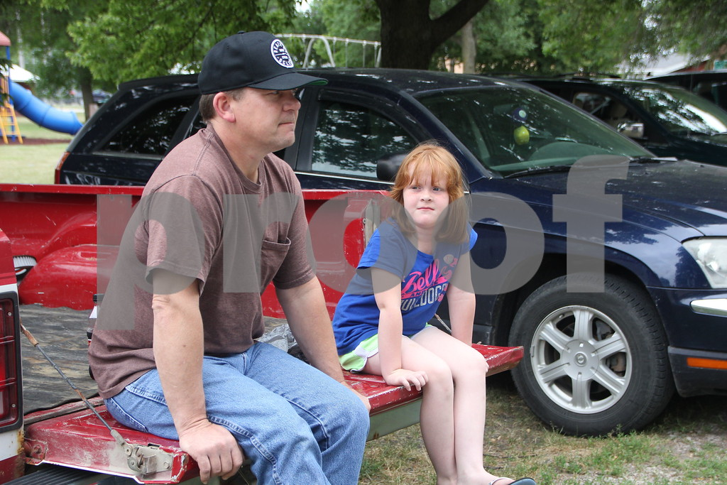 Seen left to right is: Bob and Paizley Jondle waiting for the parade to start from the back of a pickup truck. The Otho Fourth of July Parade took place in Otho on July 4, 2016.