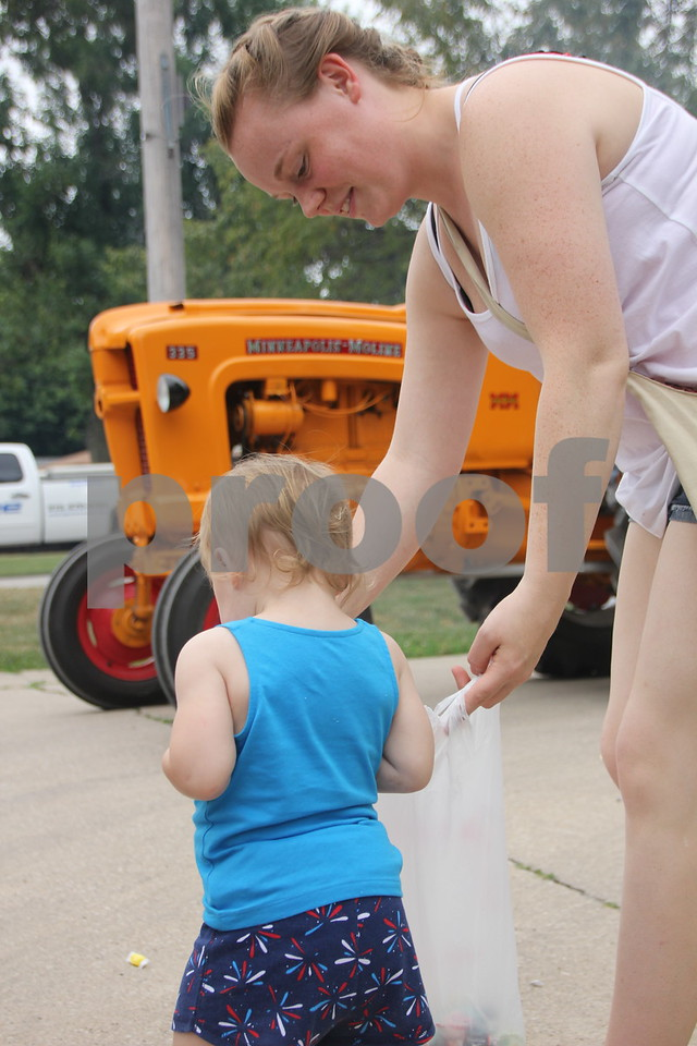 Watching the parade and enjoying the candy tossed to kids along the route is Left to right: Marlie Chase and( helping with his candy ) Lydia Henricks. The Otho Fourth of July Parade took place in Otho on July 4, 2016.