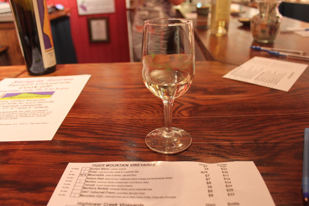 A glass of white wine sits on a countertop at a tasting room