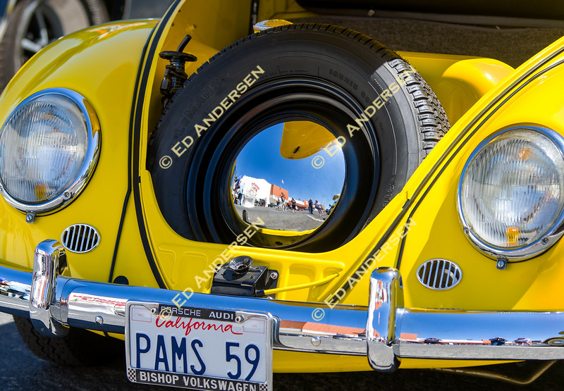 Car show enthusiasts are reflected in the spare tire's hubcap inside a 1959 Volkswagen Beetle.