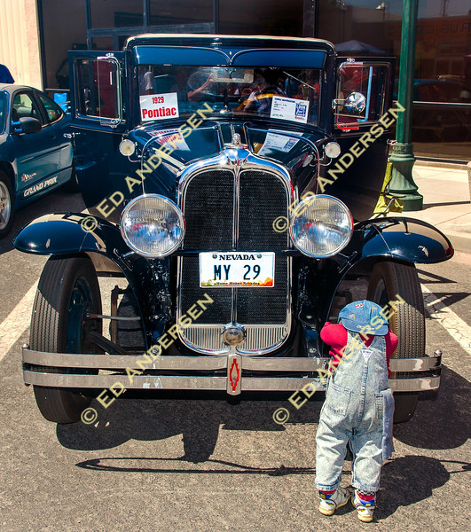 A child sized doll leans on Larry Neal's 1929 Pontiac.