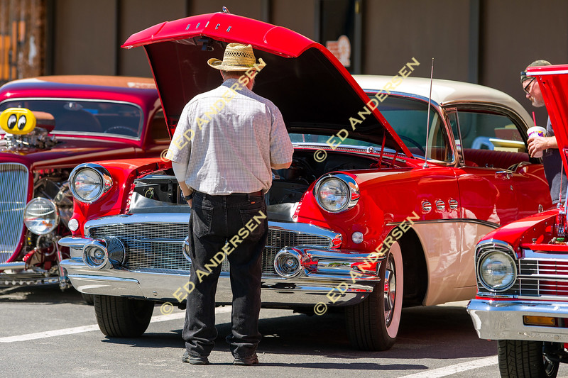 """Car enthusiasts look over a 1956 Buick, nicknamed """"The Torrid Lady"""" named for its red paint color chosen by its owner Timothy Higgins of Carson City."""