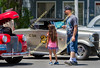 Car enthusiasts of all ages admire classic vehicles on display.