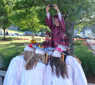 060916 Wesley Bunnell | Staff  Bristol Central High School held commencement their commencement ceremony on Thursday evening. Trevor O'Neil stands on a bench to take a group photo of friends.