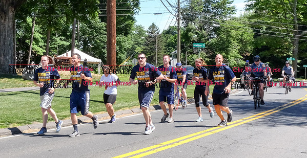 061016 Wesley Bunnell | Staff  The Law Enforcement Torch Run for the Special Olympics came through Newington, New Britain, Berlin & Southington on Friday.  The Berlin team near the intersection of Percival Ave & Sheldon St.  A bicycle cop takes a selfie towards the rear of the pack.