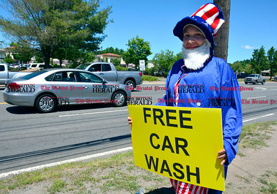 6/14/2016 Mike Orazzi | Staff Margarita Delmonte waves a  sign at on Route 6 in Bristol near Flag Car Wash & Detailing on Dallas Avenue during a free car wash promotion Tuesday afternoon.