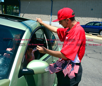 6/14/2016 Mike Orazzi | Staff Raul Deleon pass out American Flags at Flag Car Wash & Detailing on Dallas Avenue during a free car wash promotion Tuesday afternoon.