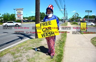 6/14/2016 Mike Orazzi   Staff Margarita Delmonte waves a  sign at on Route 6 in Bristol near Flag Car Wash & Detailing on Dallas Avenue during a free car wash promotion Tuesday afternoon.