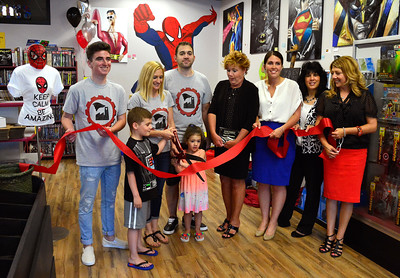 6/30/2016 Mike Orazzi | Staff Christopher and Stephanie Laudate cut the ribbon at Industry Comics in Bristol Thursday.