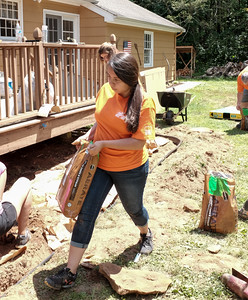 063016  Wesley Bunnell | Staff  Home Depot and volunteers came together for two days to improve a local Marine veteran's backyard.  Home Depot volunteer Brenda Salazar helping bring materials for a flower bed.