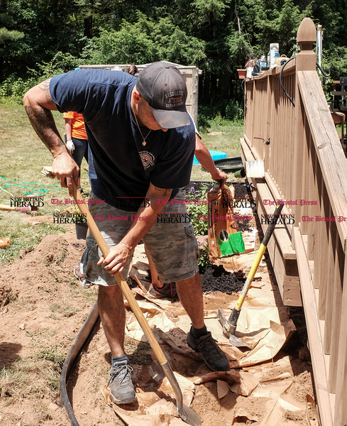 063016  Wesley Bunnell | Staff<br /> <br /> Home Depot and volunteers came together for two days to improve a local Marine veteran's backyard.  Derek Curraro digging holes for a new flower bed.