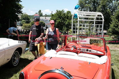 062516  Wesley Bunnell | Staff  Friends of the Barnes Museum held their second annual Wheels of the Past classic car show on Saturday morning. From L Michael Daly with Cullen McCann, age 4, and Kim Daly walk near a 1961 Nash Metropolitan convertible.
