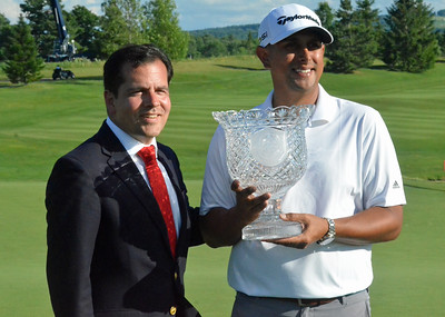 KYLE MENNIG - ONEIDA DAILY DISPATCH Rich Berberian hoists the Walter Hagen Cup alongside PGA President Derek Sprague on the 18th green of Atunyote after Berberian won the 49th PGA Professional Championship in Vernon on Wednesday, June 29, 2016.
