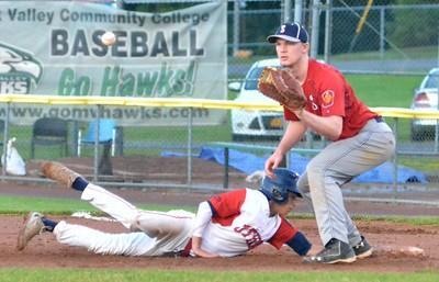 KYLE MENNIG – ONEIDA DAILY DISPATCH Utica Post's Josh Raymer (7) dives safely back into first as Sherrill Post's Davey Moffett (5) awaits a pickoff throw during their American Legion Baseball game in Utica on Tuesday, June 20, 2017.