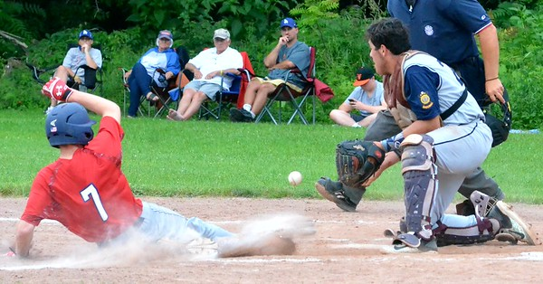 KYLE MENNIG – ONEIDA DAILY DISPATCH Sherrill Post's Zach Nell (7) slides safely into home as Helmuth-Ingalls Post catcher Thomas Labayweski (25) fields the throw during their game in Clinton on Friday, June 23, 2017.