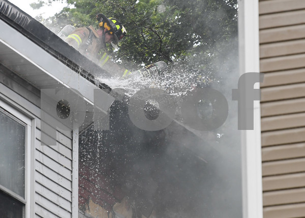 062717 Wesley Bunnell | Staff A fire broke out Tuesday afternoon at 404 East St in New Britain on the top floor. Water blasts from the inside out on the back right hand corner of the home where flames were seen.
