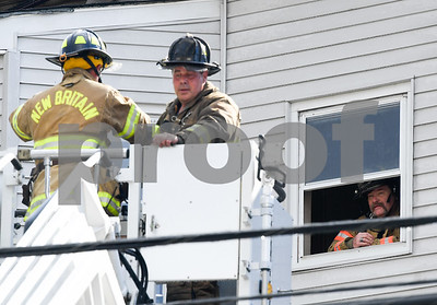 062717  Wesley Bunnell | Staff  A fire broke out Tuesday afternoon at 404 East St in New Britain on the top floor. A firefighter , R, speaks to fellow firefighters as they lower themselves onto the ladder truck from the roof.
