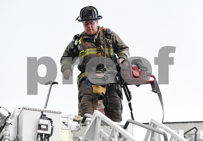 062717  Wesley Bunnell | Staff  A fire broke out Tuesday afternoon at 404 East St in New Britain on the top floor. A firefighter carries equipment towards the ladder.