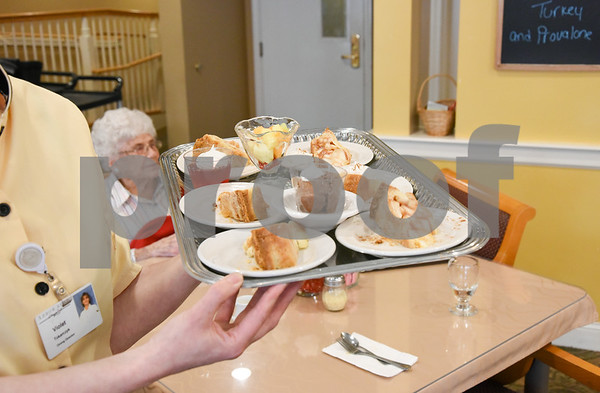 061517 Wesley Bunnell | Staff Arbor Rose residents sit enjoying their lunch on Thursday June 15. Dining Director Violette Tokarczyk walks through the dining area with a tray of desserts.