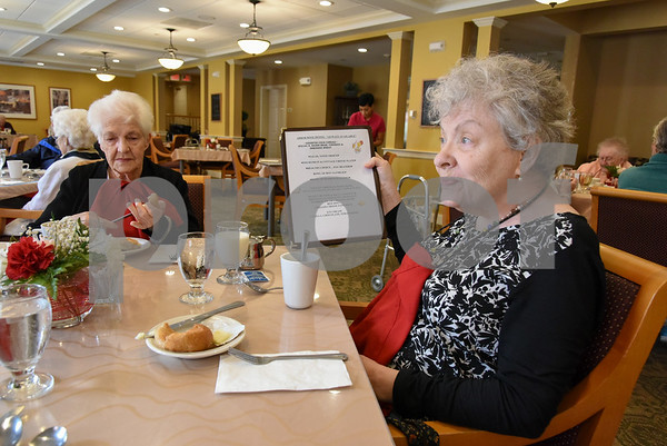 061517 Wesley Bunnell | Staff Arbor Rose residents sit enjoying their lunch on Thursday June 15. Gail Westermeyer, R, holds up the menu for the day as she sits with Pauline Gadzik who goes by Niki.