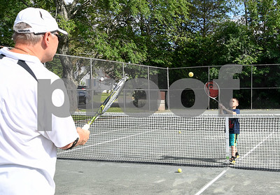 062817  Wesley Bunnell | Staff  Bob Dean gives a tennis lesson to 7 year old Anthony Morales at Mill Pond Park in Newington on Wednesday afternoon.