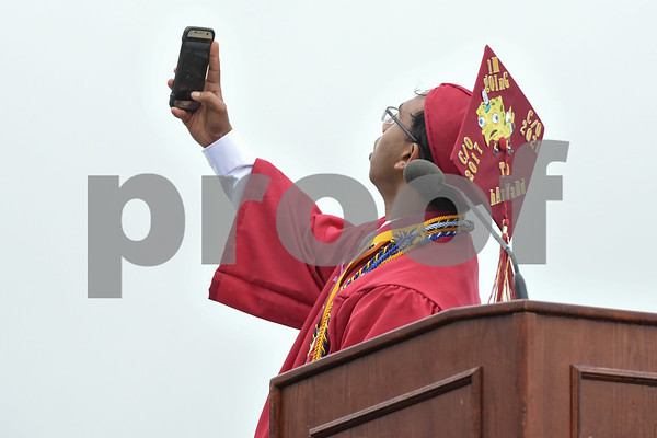 061617 Wesley Bunnell | Staff New Britain High School held graduation exercises on Friday afternoon outdoors at Veterans' Memorial Stadium despite intermittent rain showers. Valedictorian Saimum Habib takes a selfie during his address.