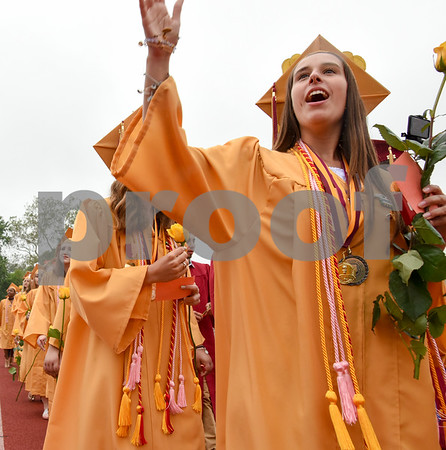 061617 Wesley Bunnell | Staff New Britain High School held graduation exercises on Friday afternoon outdoors at Veterans' Memorial Stadium despite intermittent rain showers. Students wave to family and friends as they enter pass the grandstand.