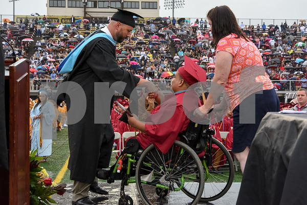 061617 Wesley Bunnell | Staff New Britain High School held graduation exercises on Friday afternoon outdoors at Veterans' Memorial Stadium despite intermittent rain showers. Principal Joseph Pinchera presents a diploma.